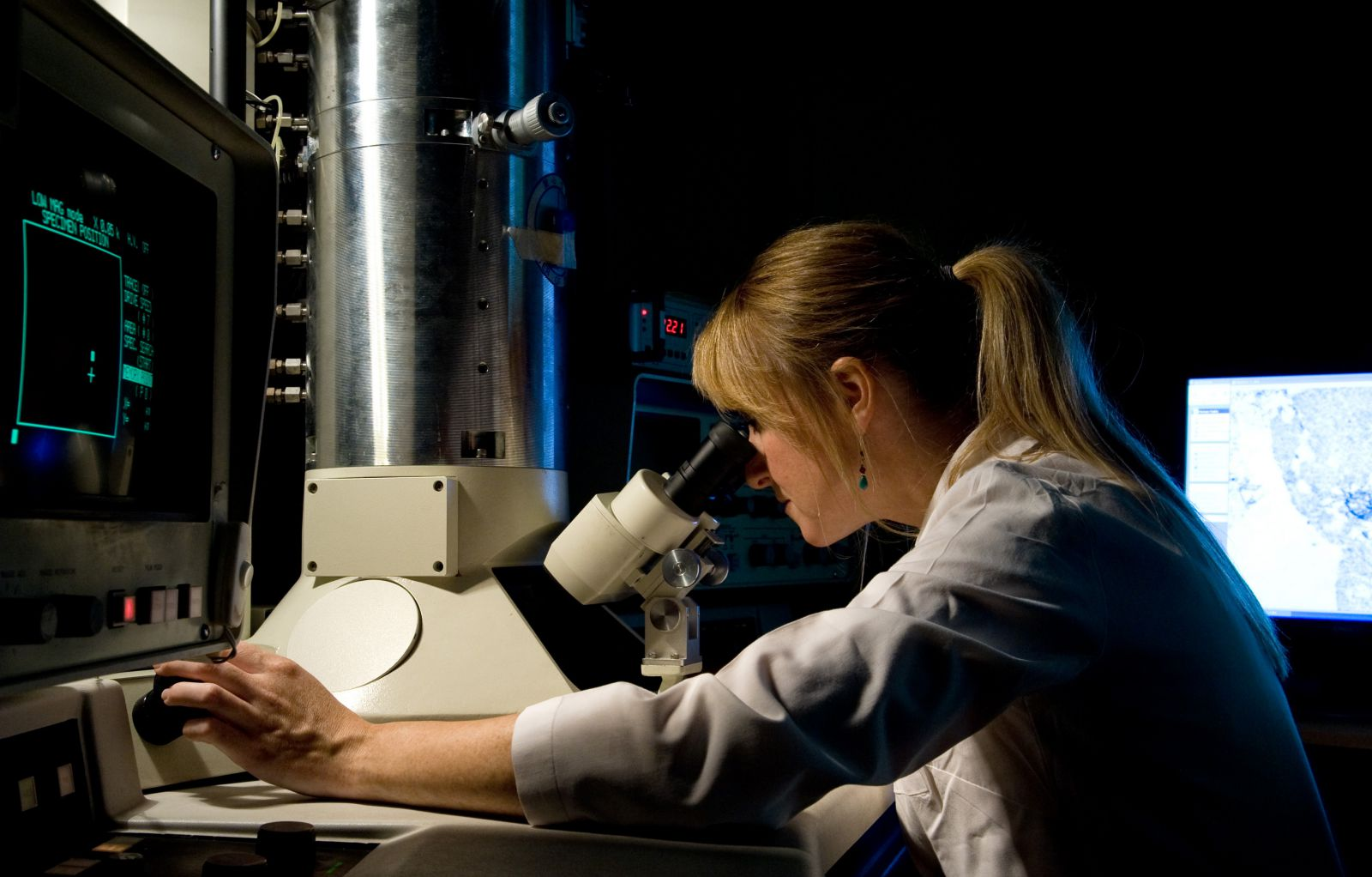 PhD student looks through a microscope in a science lab at the University of Sussex