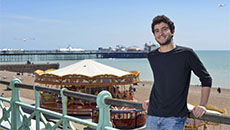 A study abroad student on Brighton seafront, with the pier and carousel behind him