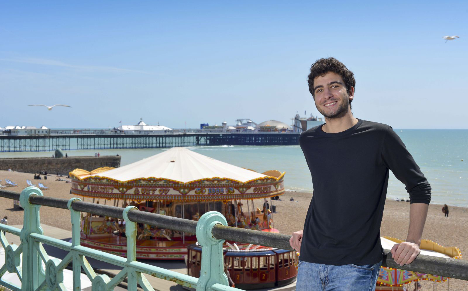 An exchange student on a study abroad experience at Sussex, standing on Brighton seafront with the pier behind him.
