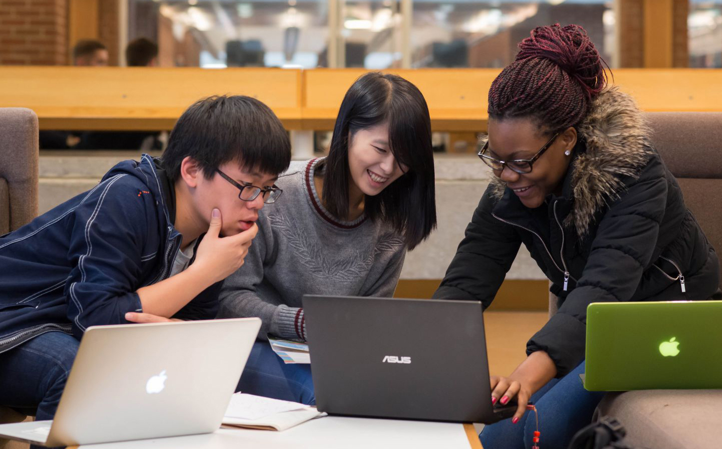 Three PhD students work together on their laptops for a project at the University of Sussex
