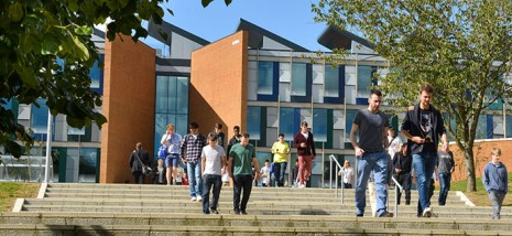 Some business students walking away from the Jubilee Building, through the trees