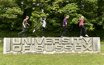 Students standing on the University of Sussex entrance sign