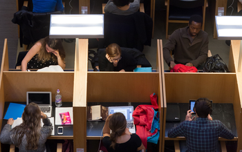 Students studying at booths in the library