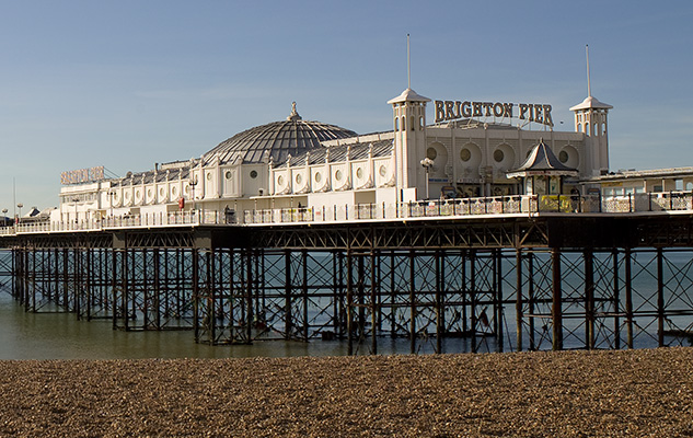 Brighton Pier seen from the left-hand side of the entrance as dusk sets in