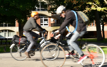 Two cyclists breezing through the University of Sussex campus on a sunny day