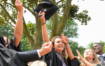 New graduates toss their hats, known as mortar boards, into the air