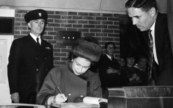 The Queen signing a document at the University of Sussex