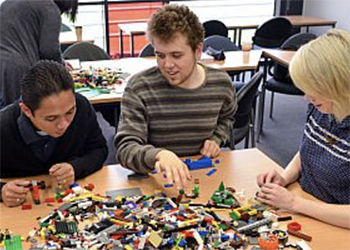 Three people building shapes with lego bricks