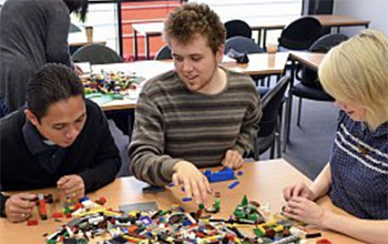Three people building with lego at the University of Sussex