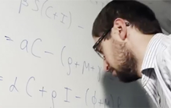 An academic writing mathematical equations on a whiteboard at the University of Sussex