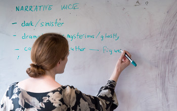 An academic writing on a whiteboard at the University of Sussex