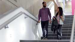 An academic and a student talking and walking down stairs together in the Jubilee Building, home to the University of Sussex Business School
