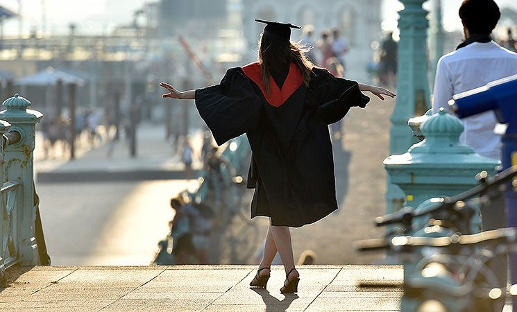 A student wanders on to the seafront in the sunshine after graduating