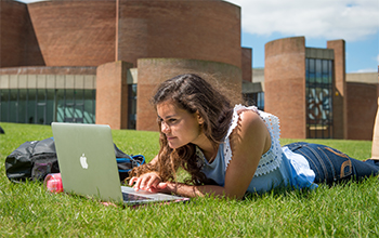 Student studying on campus in the sunshine at the University of Sussex