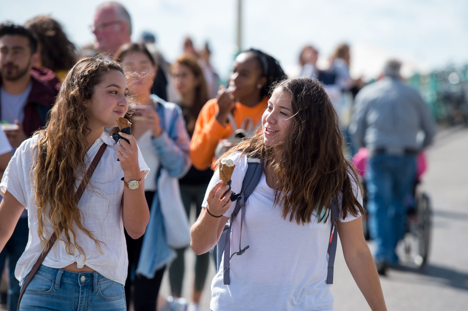 Students walking along Brighton seafront with ice creams
