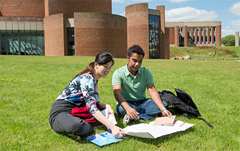 Two students sitting in front of ACCA on the grass in the sunshine at the University of Sussex
