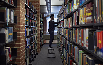 A student choosing a book in the library at the University of Sussex