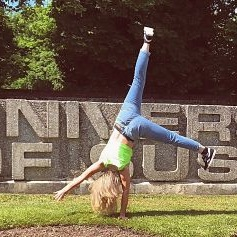 Lauren - Sussex student doing a cartwheel in front of the Sussex sign