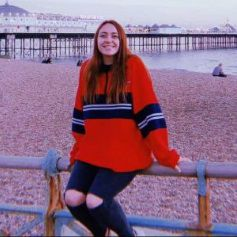 Georgina, a student graduate, sitting on the rail infront of Brighton pier