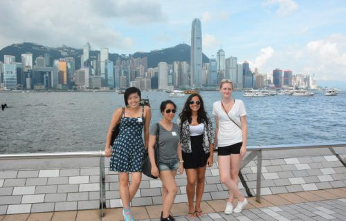 Icon students standing in front of a city skyline in Asia