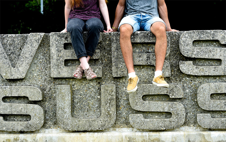 Two students sitting on the University of Sussex sign