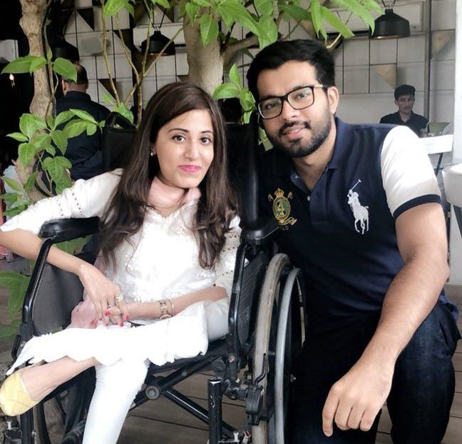 Photo of Muhammad and his friend and partner Amna. Muhammad is kneeling to the right of Amna, who is sitting in her wheelchair. Both are smiling at the camera