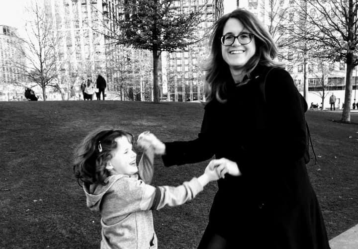 A black and white photo of Sarah-Jane and her daughter. They're holding hands and dancing outside on a wall, by a grass area in a city